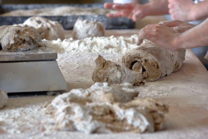 面包的贝克揉的面团在面包店 免版税库存图片
