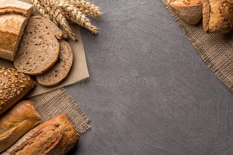 面包背景用麦子,与五谷的芳香薄脆饼干,拷贝空间,顶视图 布朗和白色整个五谷大面包静物画 免版税图库摄影
