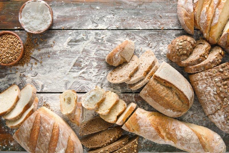 面包面包店背景 布朗和白色麦子五谷大面包构成在土气木头 免版税库存照片