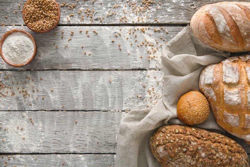 面包面包店背景 布朗和白色麦子五谷大面包构成在土气木头 库存照片