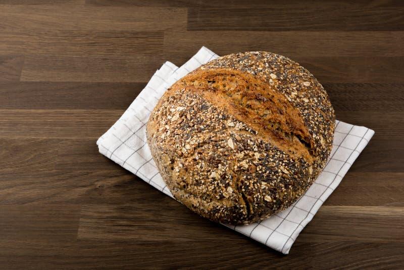 面包,用在洗碗布,木背景的种子盖的新鲜的健康黑面包 库存照片