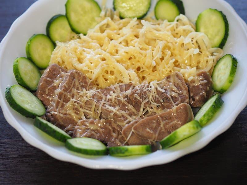 面团、搓碎干酪、煮沸的舌头和新鲜的黄瓜关闭  免版税库存照片