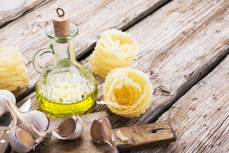 面团、橄榄油、新鲜的大蒜、草本和草厨房简单的静物画  免版税库存图片