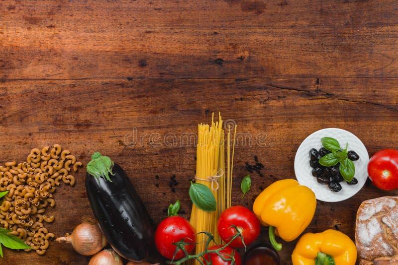 面团、菜、草本和香料意大利食物的在土气木桌上,顶视图,拷贝spac 免版税库存图片