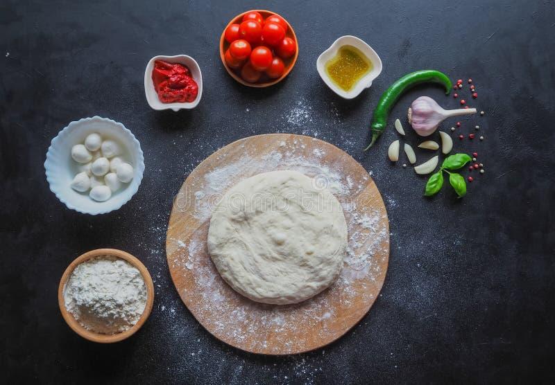 面团和一套在一张黑桌上的薄饼成份 意大利薄饼玛格丽塔的生产 生产阶段 免版税图库摄影