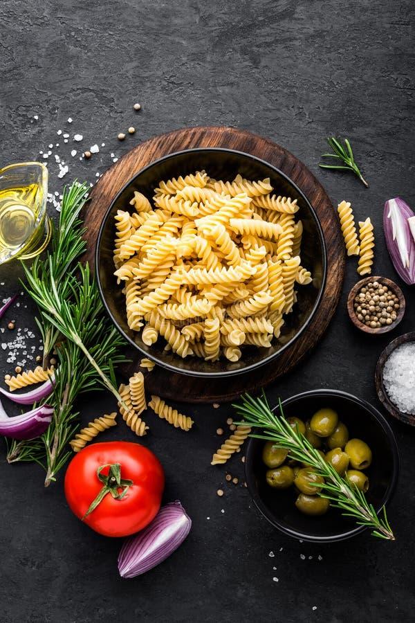 面团和成份烹调的在黑背景,顶视图 烹调意大利语的食品成分 免版税库存照片