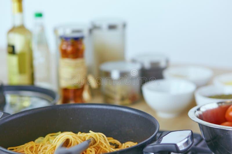 面团在叉子滚动了在火炉的平底锅在厨房里 免版税图库摄影