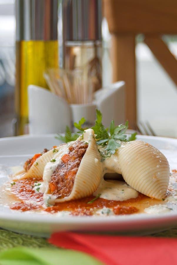面团壳conchiglioni用填装在盘的调味汁特写镜头的肉末 免版税库存照片