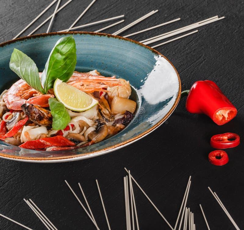 面团意粉用海鲜,海螯虾,淡菜,牡蛎,在蘑菇酱油的乌贼在黑暗的石背景的板材 意大利语 免版税库存图片