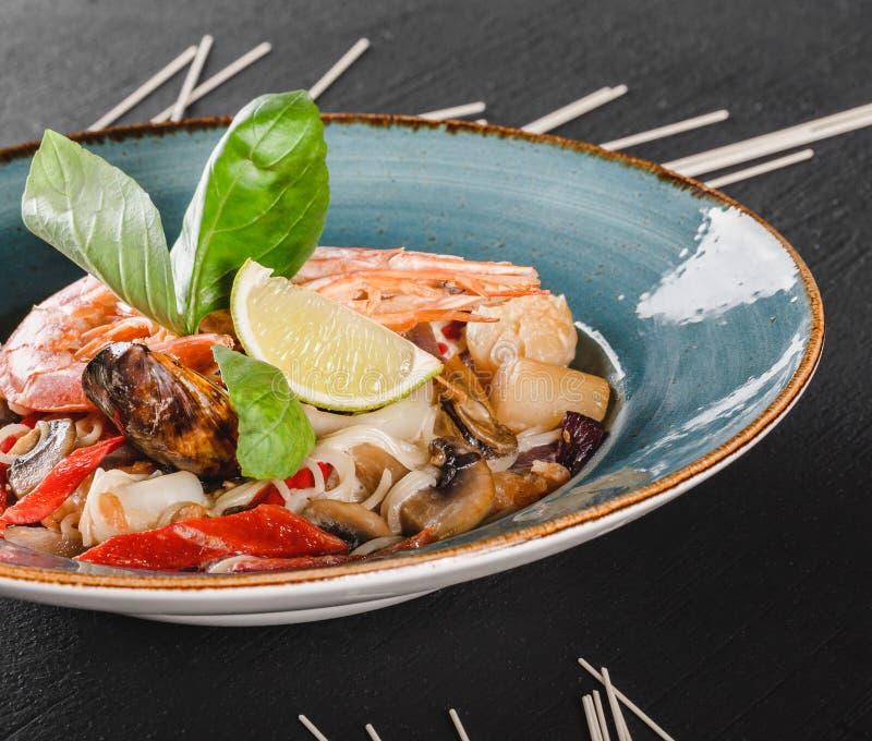 面团意粉用海鲜,海螯虾,淡菜,牡蛎,在蘑菇酱油的乌贼在黑暗的石背景的板材 意大利语 库存图片