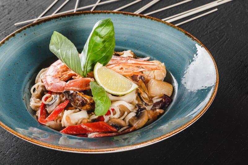面团意粉用海鲜,海螯虾,淡菜,牡蛎,在蘑菇酱油的乌贼在黑暗的石背景的板材 免版税库存照片