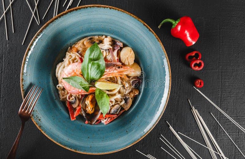 面团意粉用海鲜,海螯虾,淡菜,牡蛎,在蘑菇酱油的乌贼在黑暗的石背景的板材 图库摄影