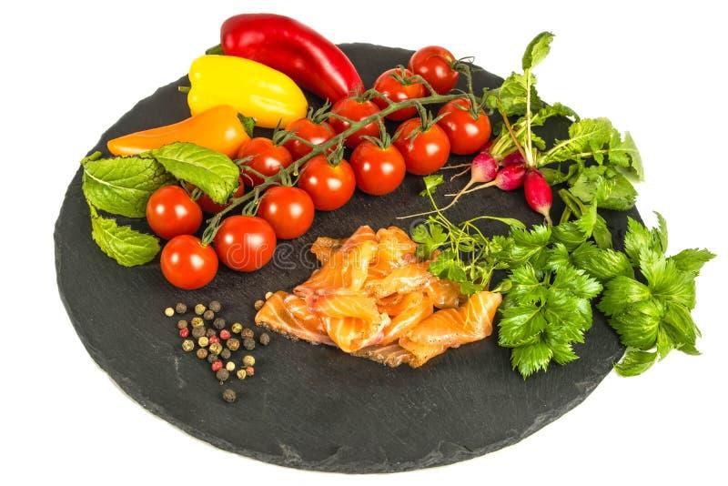 面团新鲜的蕃茄,胡椒,鱼,在黑石板,白色背景的萝卜的构成 免版税库存照片