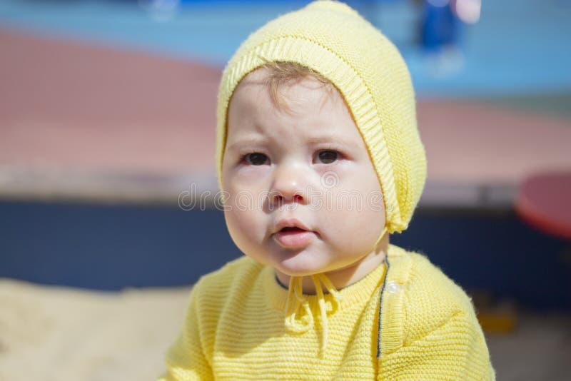 面孔女婴男孩画象特写镜头 户外一个黄色编织帽子的孩子 免版税库存照片