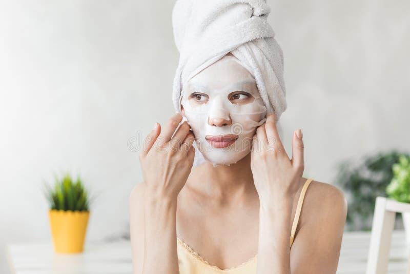 面孔护肤 在毛巾包裹的可爱的年轻女人,与白色润湿的面膜 护肤概念 库存照片