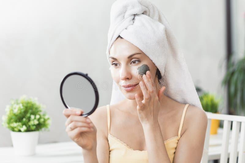 面孔护肤 在毛巾包裹的可爱的年轻女人,应用黏土泥面具面对 护肤概念 女孩 免版税库存照片