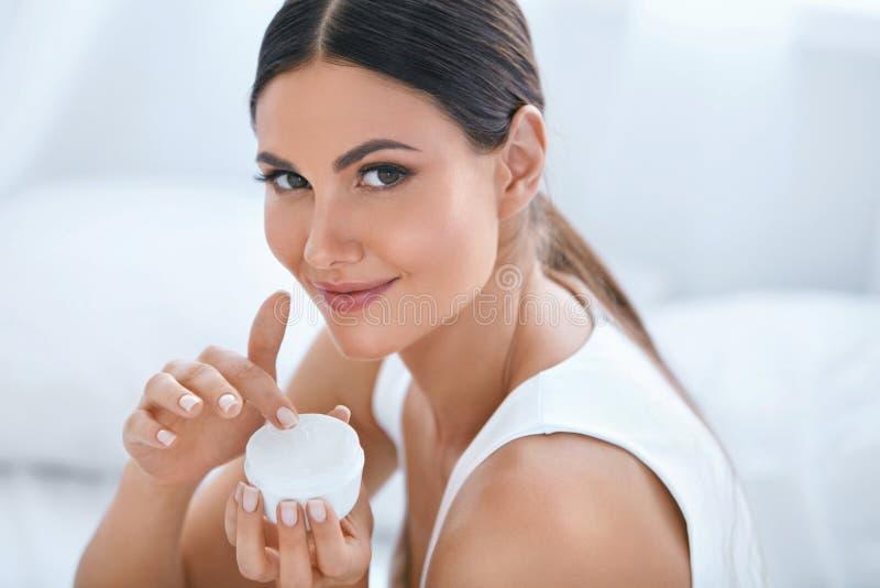 面孔护肤 有面部奶油的美丽的妇女 化妆用品 免版税库存照片
