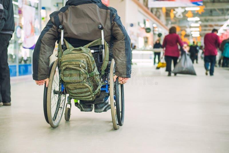 面孔没有变老轮椅的残疾,残疾人在人中没有在市场购物中心的伤残  Selectiv 免版税图库摄影