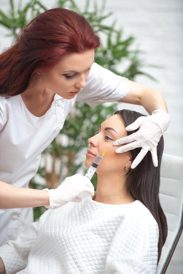 面孔的补白射入 塑料审美面部手术 给与注射器的医生妇女射入注射嘴唇和botox 库存照片