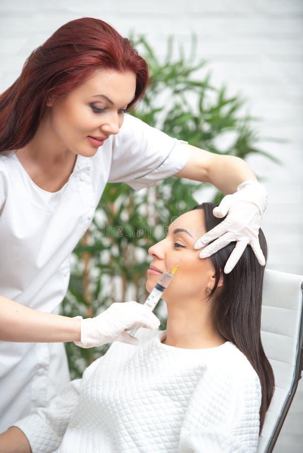 面孔的补白射入 塑料审美面部手术 给与注射器的医生妇女射入注射嘴唇和botox 库存图片