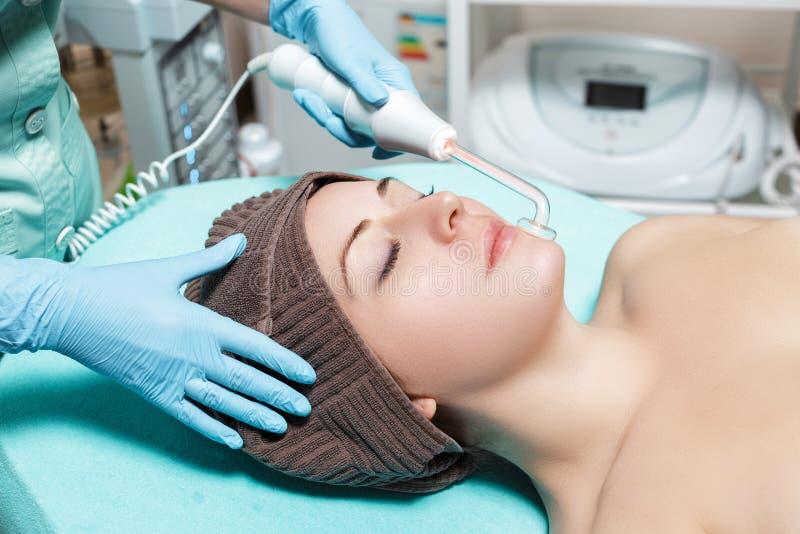 面孔秀丽治疗 美容师做妇女的面部Darsonval疗法 库存照片