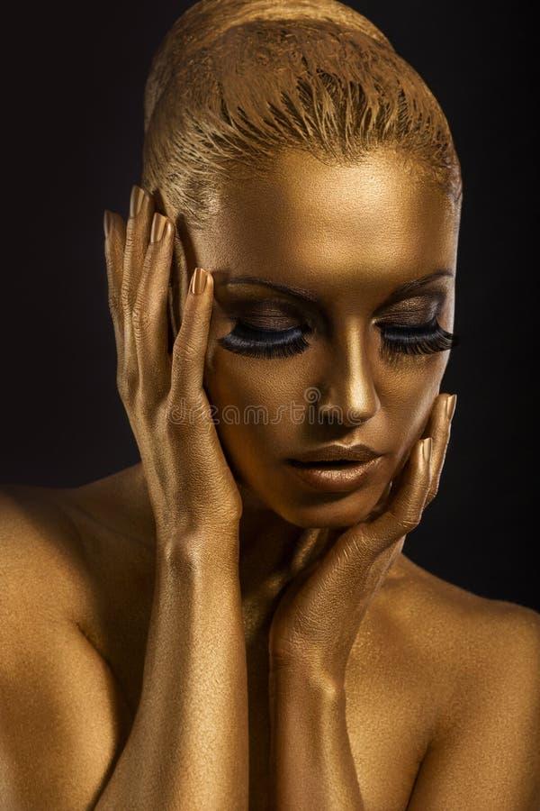 面孔艺术。 意想不到的金子组成。 风格化色的妇女的身体 库存照片