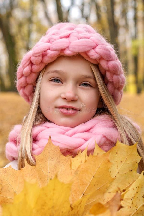 面对一个沉思梦想的微笑的女孩的画象一个概略的手工编织的圣诞节冬天的帽子和围巾的 库存照片