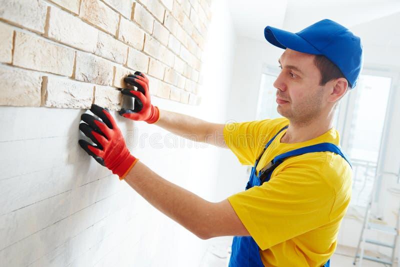 面对与砖一起使用的墙壁由专业瓦工工作者 免版税库存照片