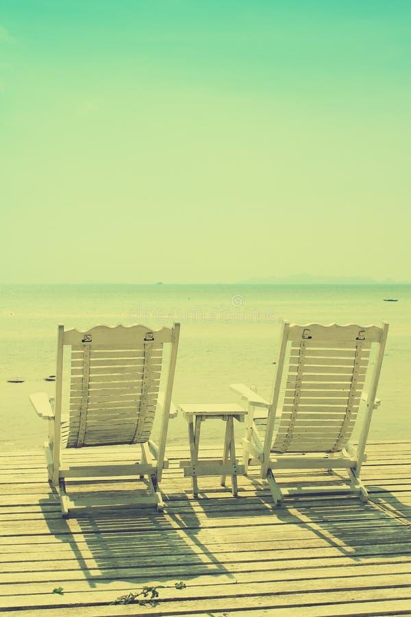 面对与葡萄酒的舒适白色海滩睡椅海景过滤了图象 免版税库存图片