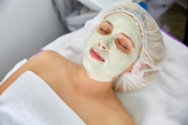 面对削皮面具,温泉秀丽治疗, skincare 可及面部关心由美容师温泉沙龙,侧视图,特写镜头的妇女 库存照片