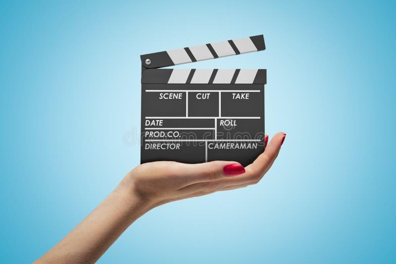 面对和举行在浅兰的梯度背景的妇女的手旁边特写镜头clapperboard 库存图片