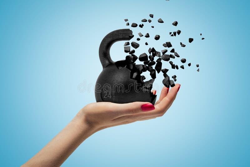 面对和拿着24kg溶化入在浅兰的小片断的kettlebell的妇女的手旁边特写镜头 图库摄影