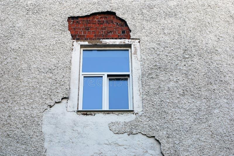 面对在最近安装的窗架附近的被破坏的墙壁 免版税库存照片