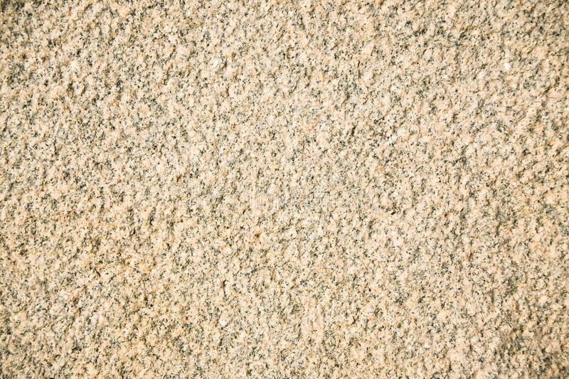 面对平板的一块米黄花岗岩的片段 自然米黄花岗岩未经治疗的粗糙的石表面  库存图片