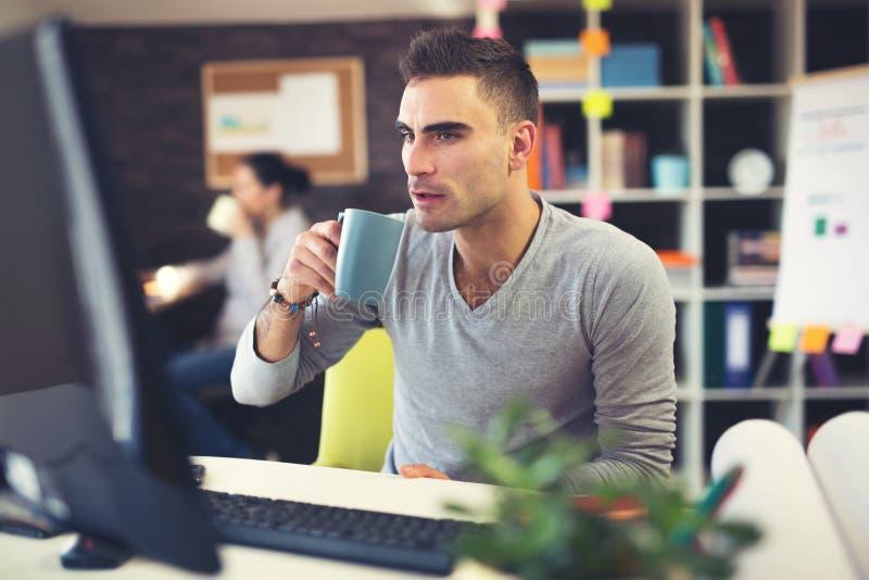 面对平面屏幕计算机的工作书桌的白种人人 免版税库存图片