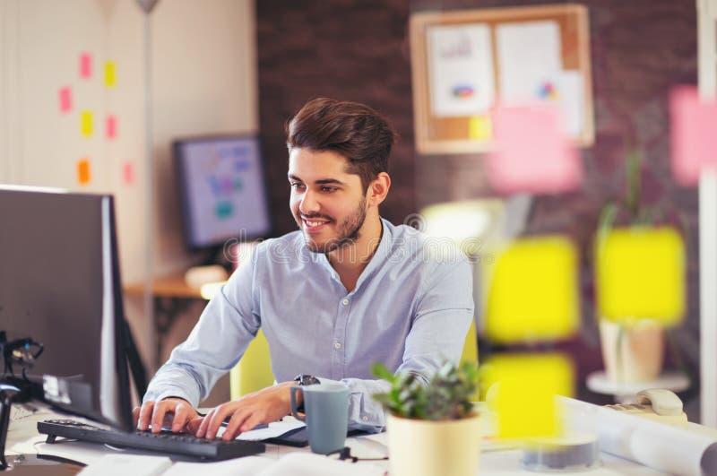 面对平面屏幕计算机的工作书桌的英俊的白种人人 免版税图库摄影