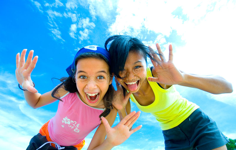 面对有乐趣滑稽的女孩做年轻人 库存图片