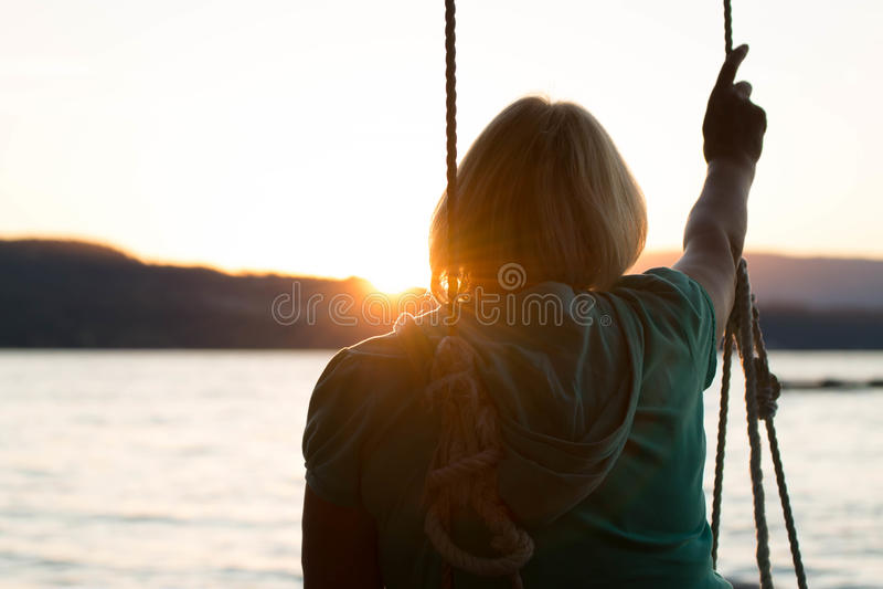面对海洋的摇摆的成熟妇女 图库摄影