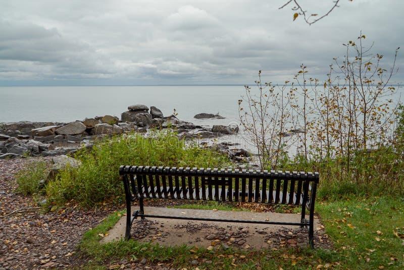 面对苏必利尔湖畔的岩石岸公园长椅在明尼苏达北部在一阴天 库存照片