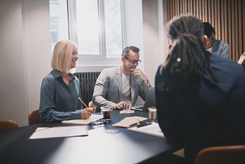 面带微笑的商人围着会议桌一起工作 免版税库存图片