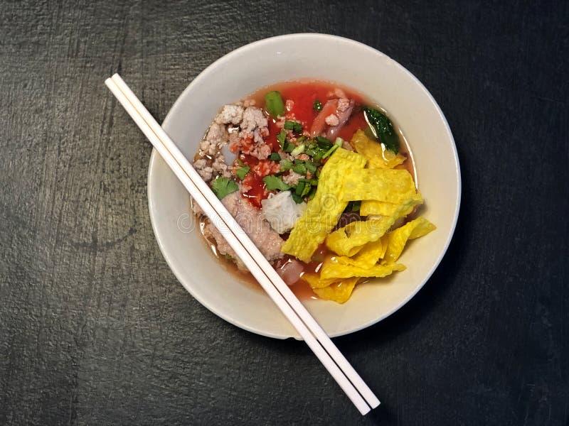 面条和猪肉在桃红色汤在黑桌上,可口泰国食物 免版税库存图片