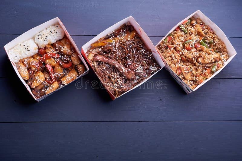 面条用猪肉和菜在外卖箱子在木桌上 图库摄影
