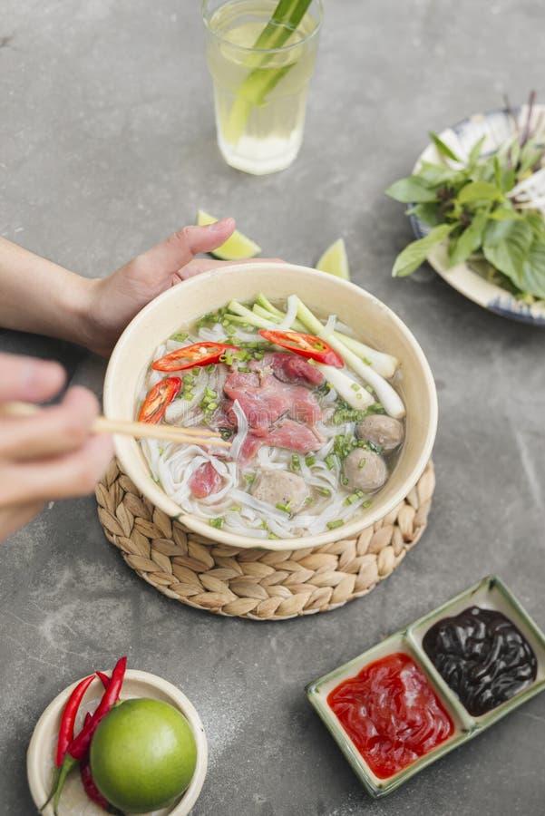 面条pho汤越南语 牛肉用辣椒,蓬蒿,米粉,显示面条的豆射击拾起与筷子 免版税库存照片