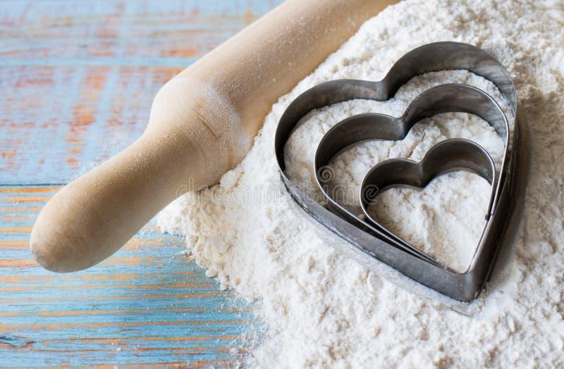 面粉、滚针和三烘烤的心脏在白色小麦面粉中在蓝色木包伙食 图库摄影