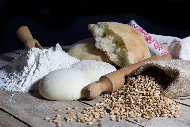 面粉、面团、面包、滚针和黄麻袋子充满在木表上的麦子在黑背景 库存照片