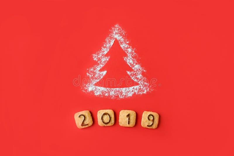 面粉剪影与曲奇饼数字的圣诞树2019年在红色背景 可口面包店甜糖果店圣诞卡 库存照片