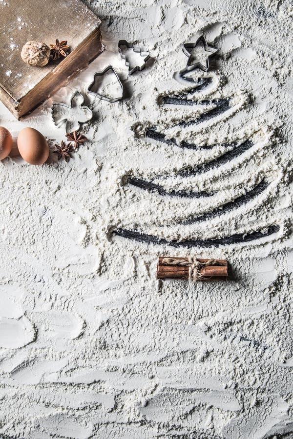面粉和老食谱书形状的圣诞树  免版税库存图片