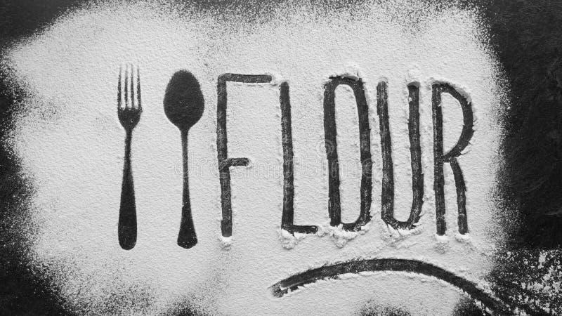 面粉在与匙子和叉子剪影的面粉写做用面粉在黑暗的纹理背景 免版税图库摄影