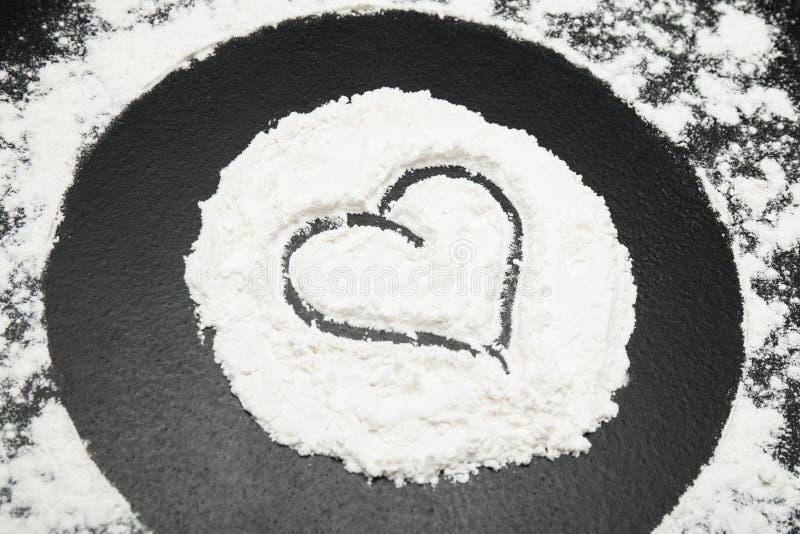 面粉的心脏在黑背景的 免版税图库摄影