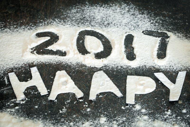面粉的新年2017年题字在桌上的 免版税库存照片